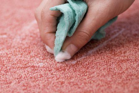A Hand Scrubbing Red Carpet