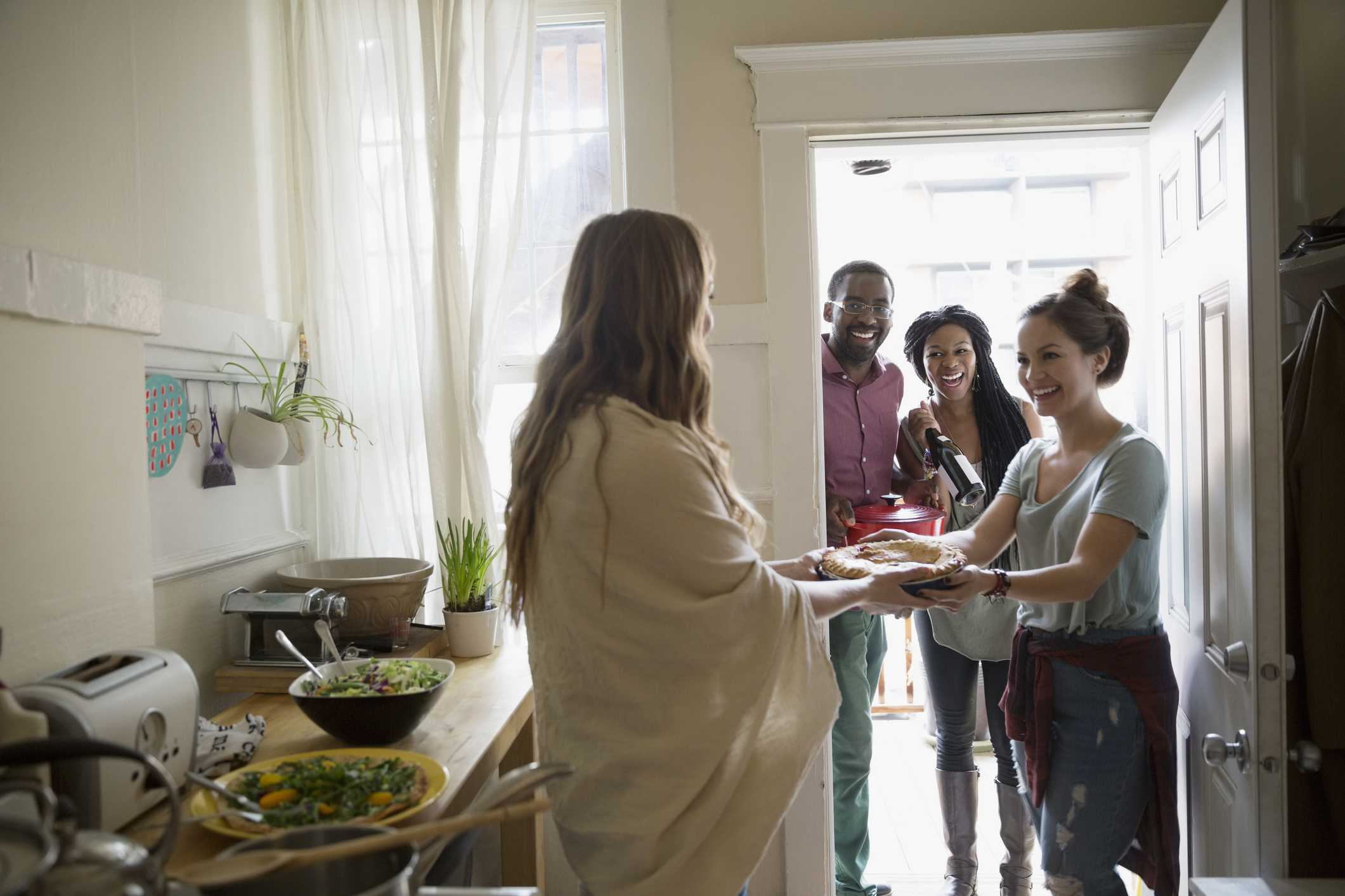 Woman greeting friends arriving for potluck dinner party