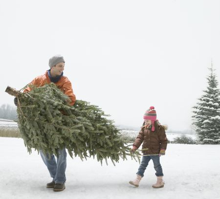 a man carrying a christmas tree with his daughter - Best Kind Of Christmas Tree