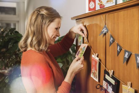 Etiquette tips for sending holiday cards woman hanging up holiday cards for decoration m4hsunfo