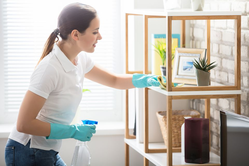 Woman cleaning shelf