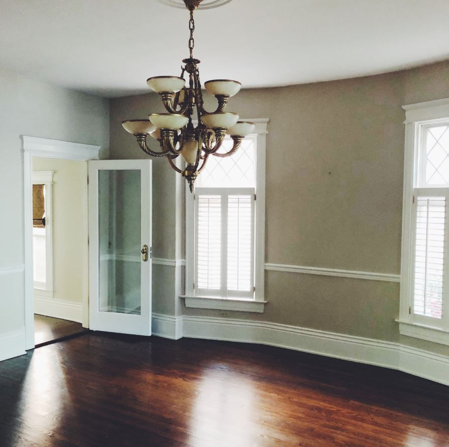 Empty, traditional dining room with brass chandelier.