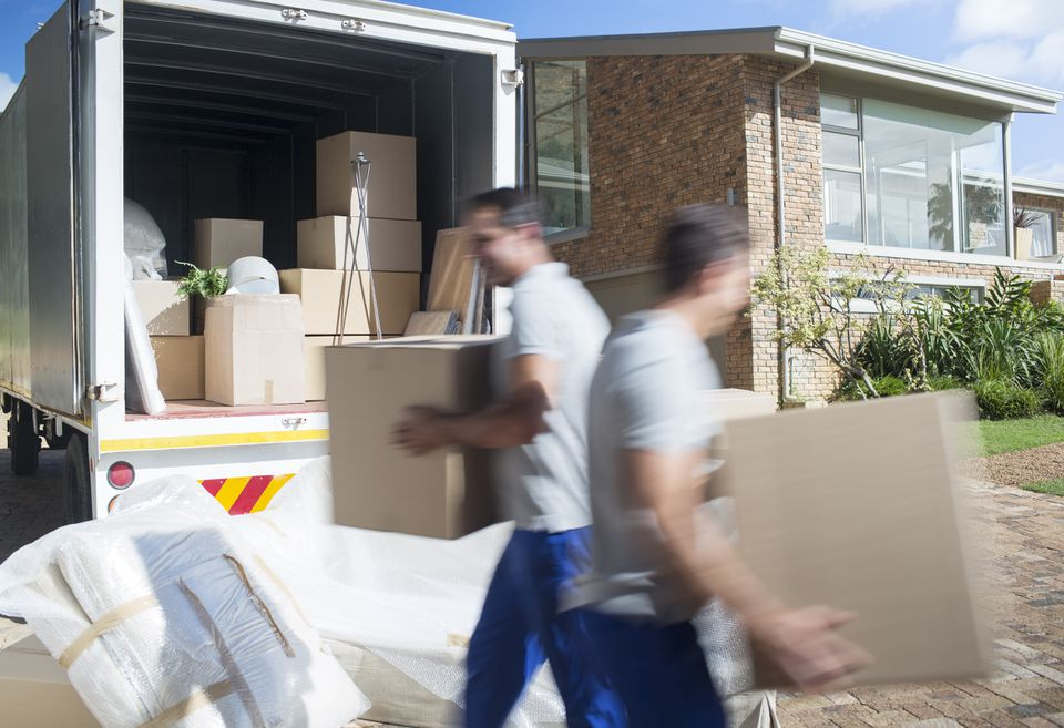 Movers carrying cardboard boxes in driveway