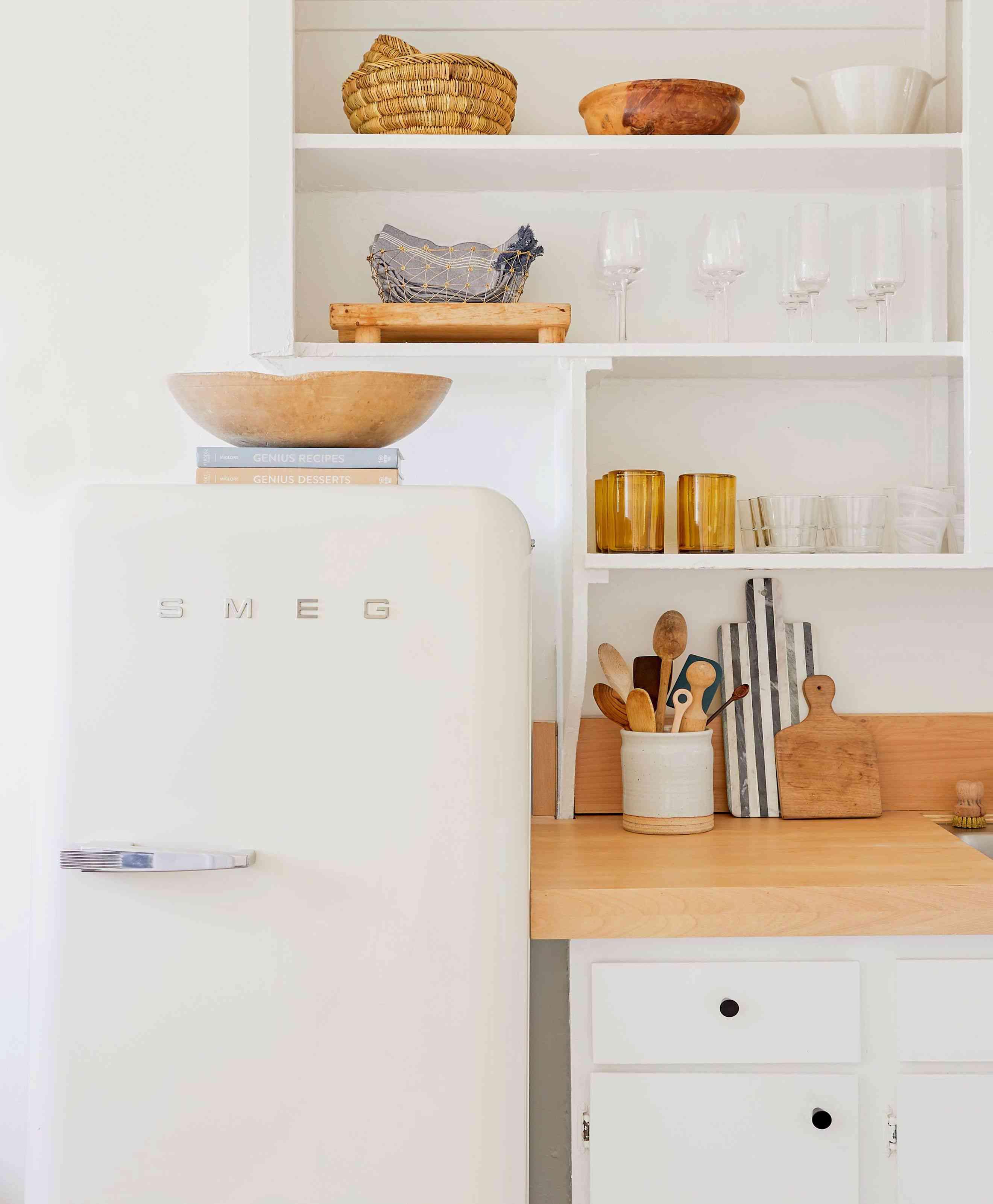 white modern kitchen with retro fridge cookbooks and bowl on top of fridge