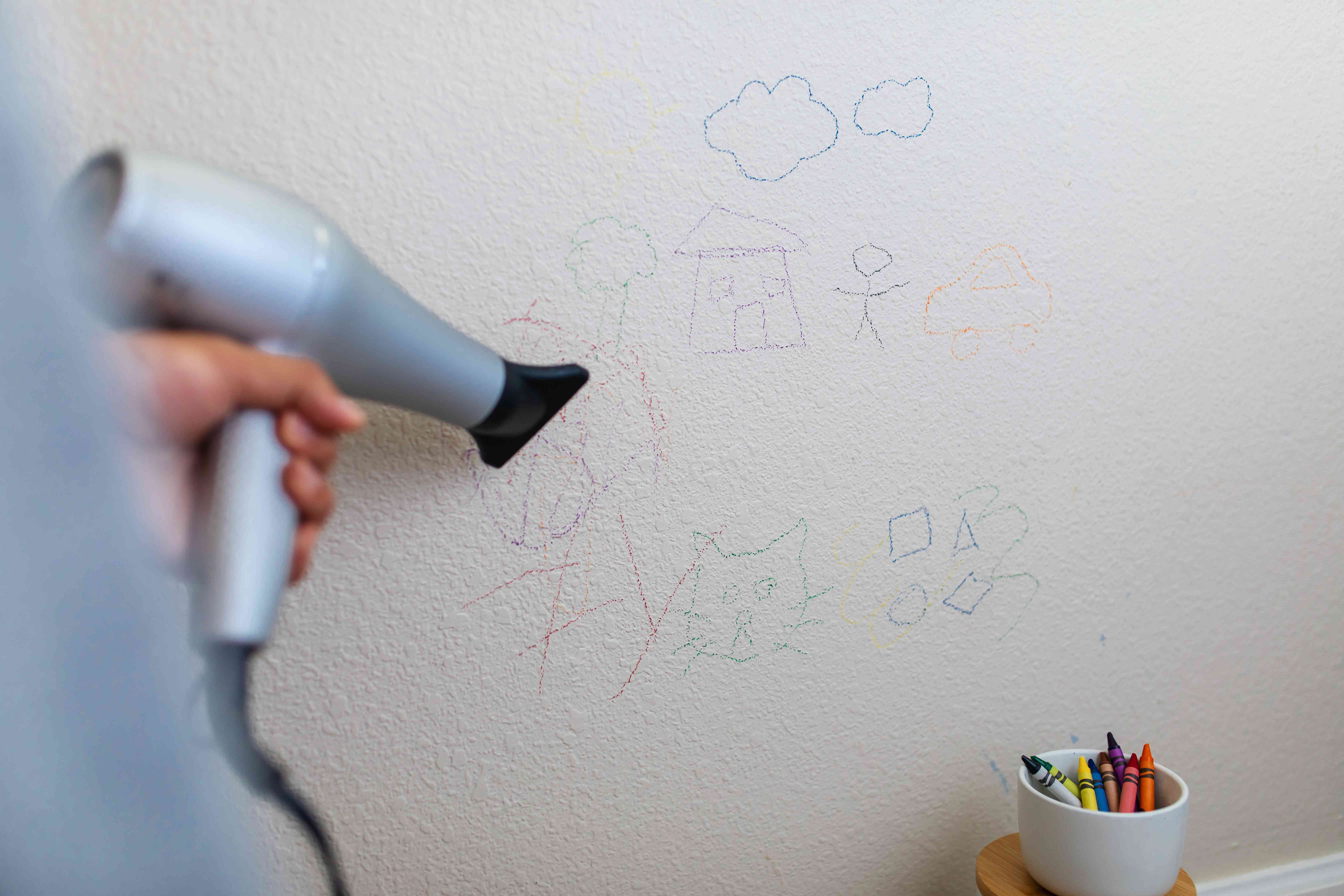 person using a blow dryer and dish soap to remove crayon stains