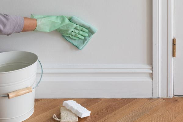 White wall being cleaned with green microfiber cloth and gloved behind white bucket and sponges