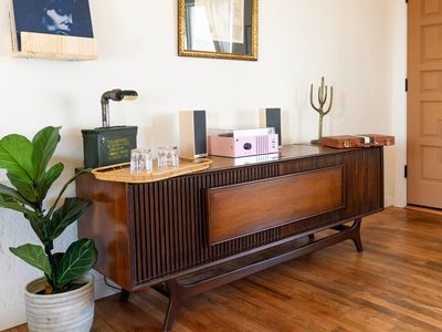 Mid-century modern style cabinet next to fiddle leaf fig plant with decor items on top