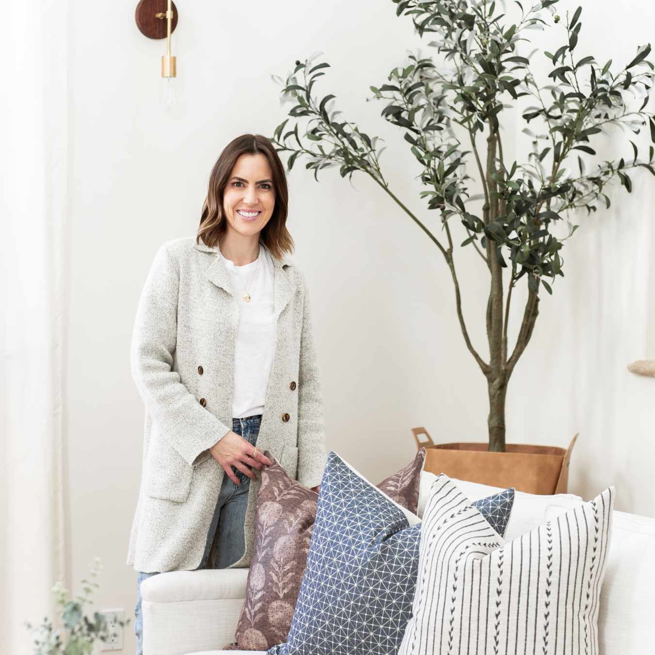 Lauren Meichtry poses in a room near a plant and couch