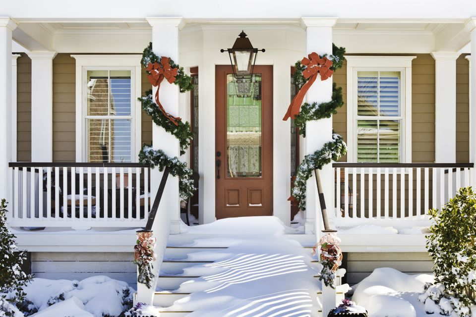 inviting Christmas front doorway with snow on porch stairs and garlands on columns.