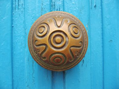 Ornate doorknob on a blue door.