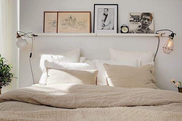Bed with linen bedding and a shelf overhead