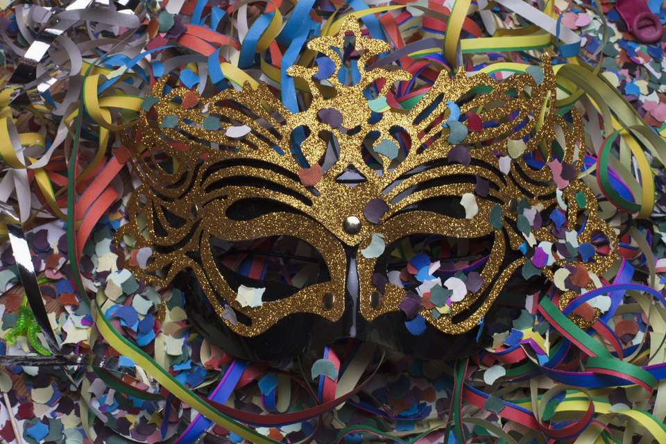 A typical Mardi Gras mask covered in confetti.