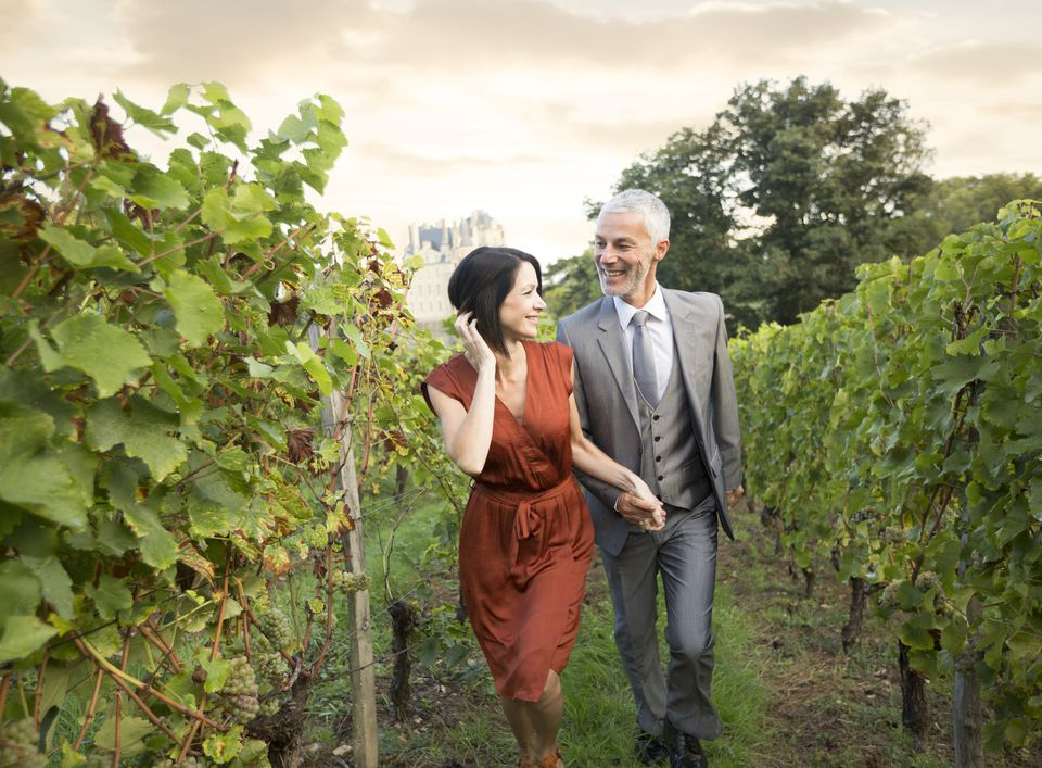 Caucasian couple walking in vineyard