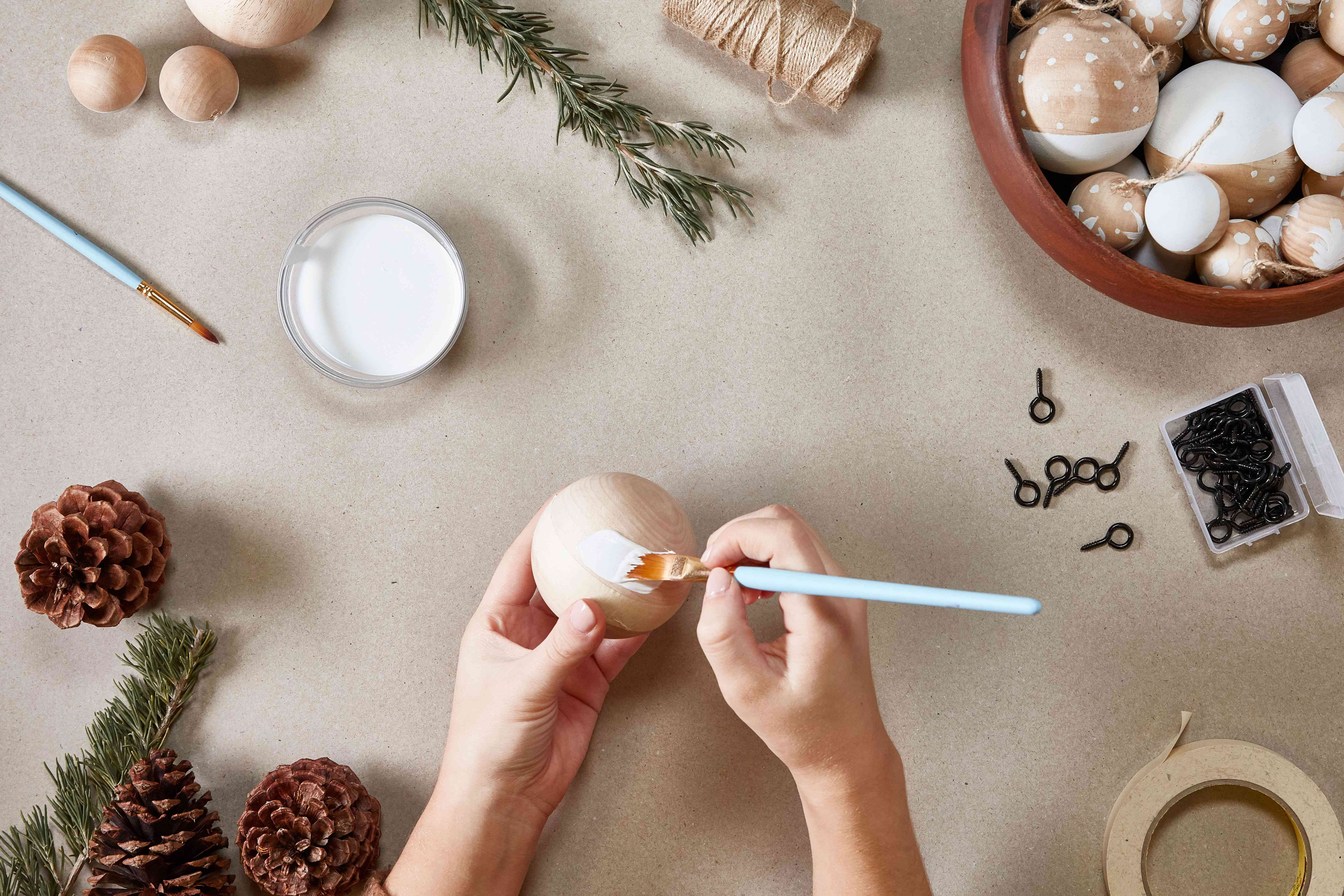 Hands painting a wooden ornament