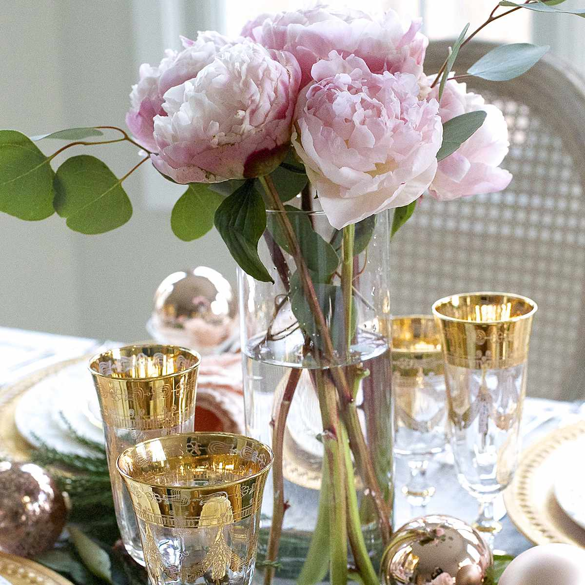 Table with gold-plated glassware and a vase of pink peonies.