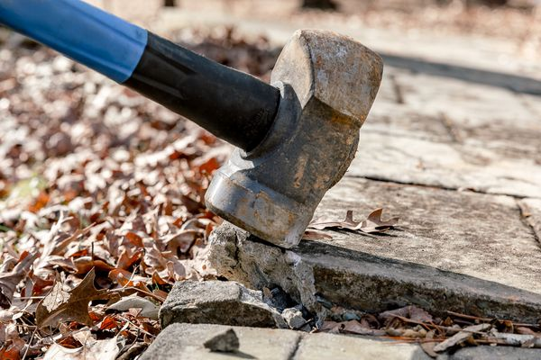 breaking up concrete with a sledgehammer