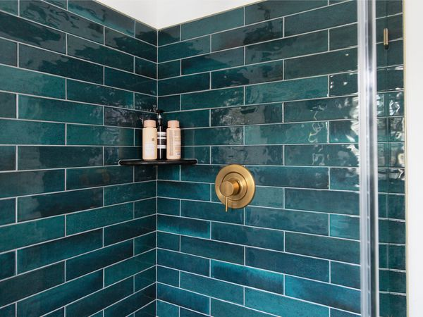Deep teal bathroom tiles in a shower stall