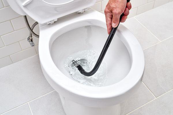 Toilet auger unclogging a toilet trap
