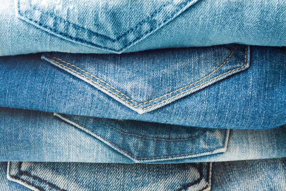 Stack of blue jeans closeup