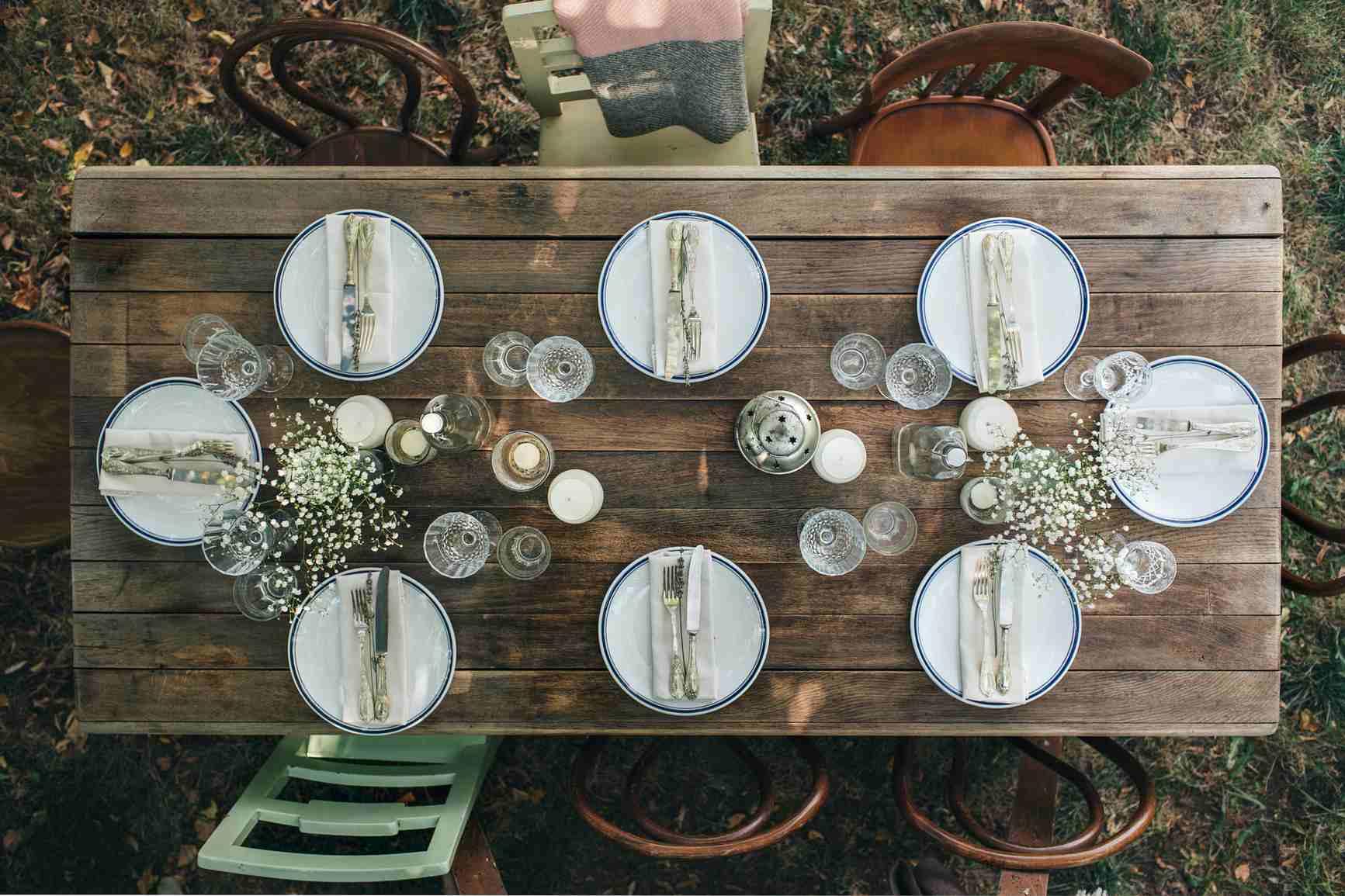 mesa de madera con platos, cubiertos y sillas afuera