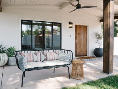 Outdoor patio with white walls and black framed windows behind outdoor seating