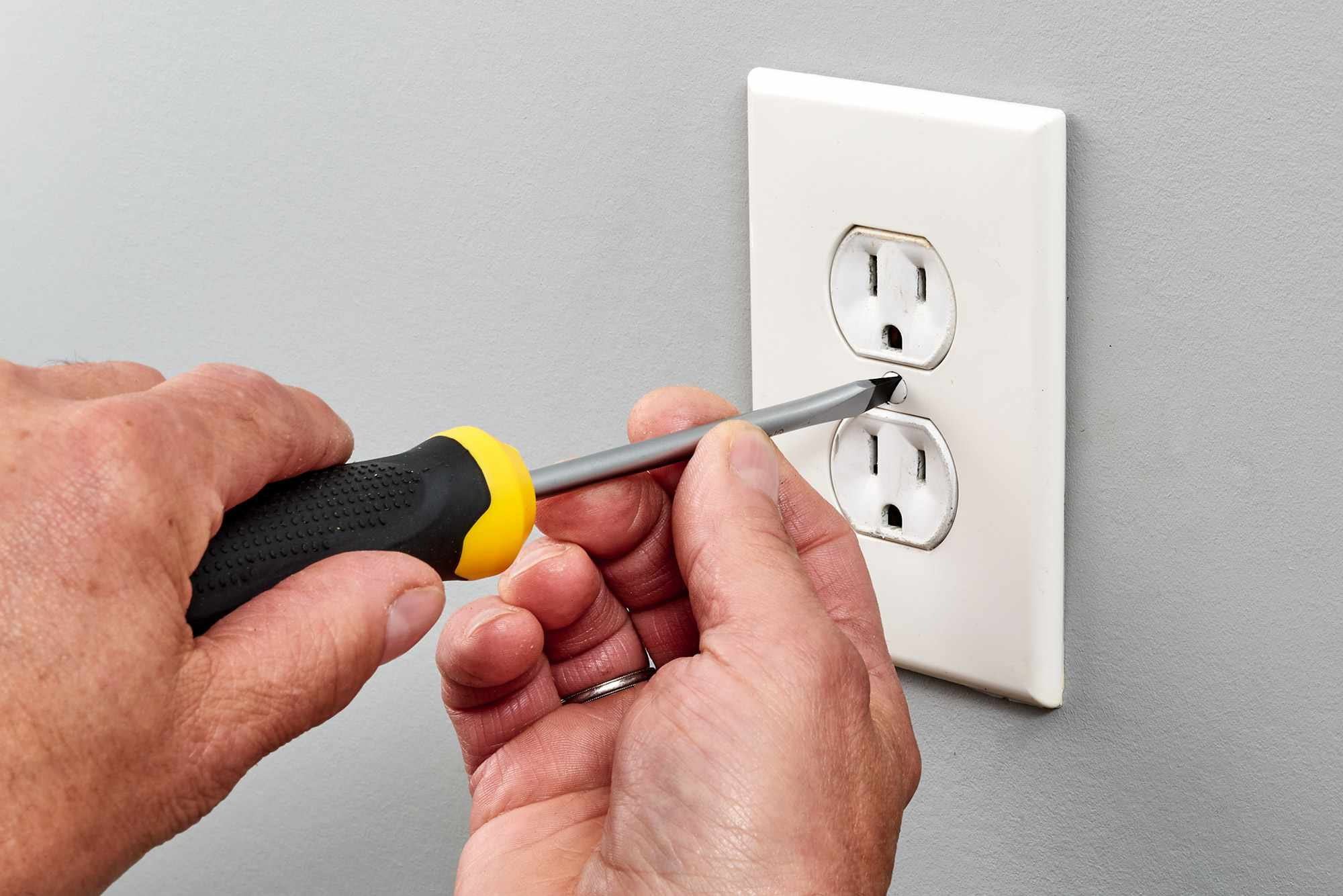 Center screw of outlet faceplate unscrewed with screwdriver
