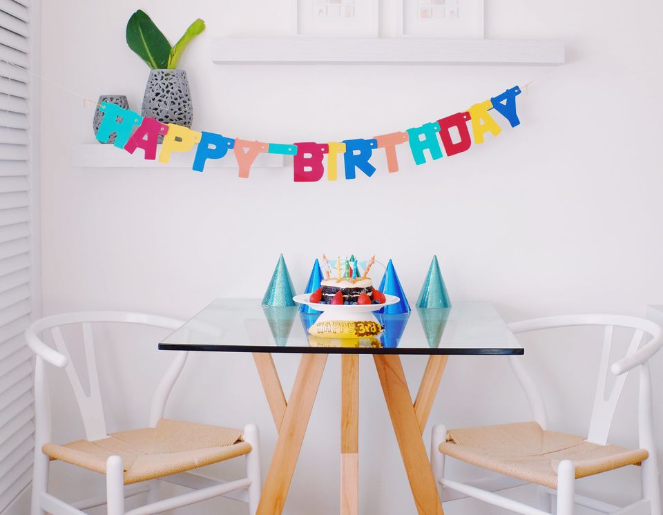 Happy Birthday banner hanging over a table with a birthday cake and birthday hats