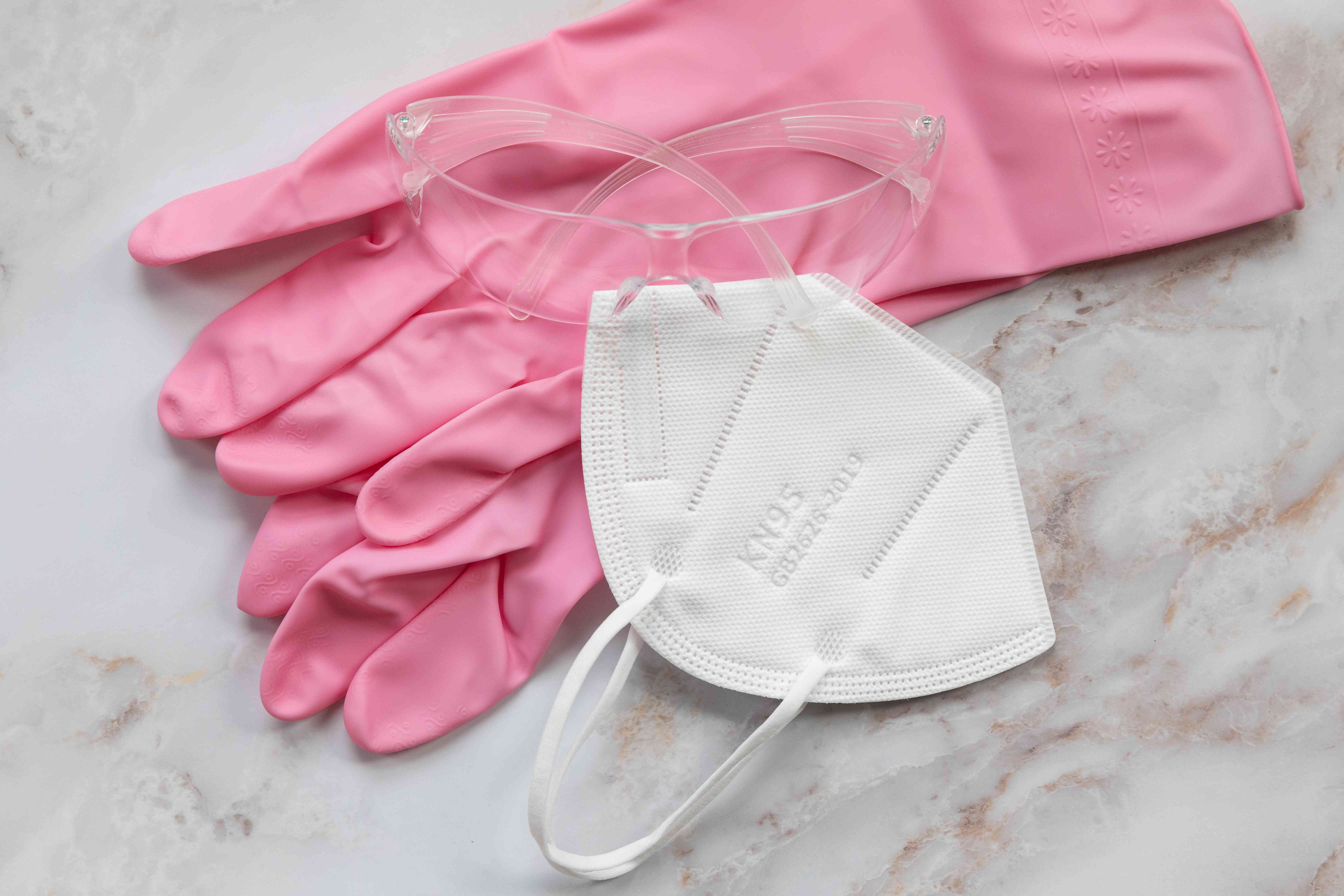 Pink gloves next to protective eyewear and white mask