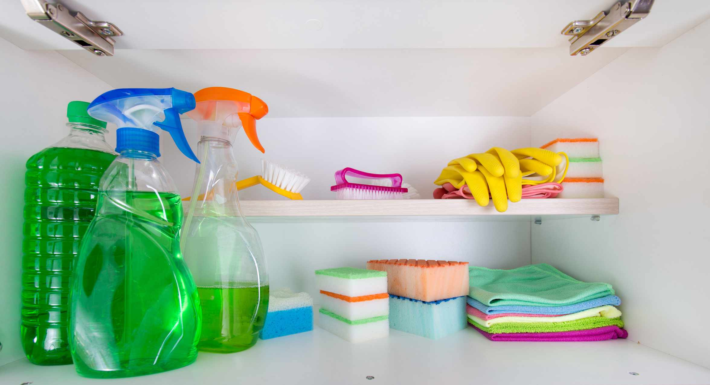 Cleaning supplies in a white cabinet.