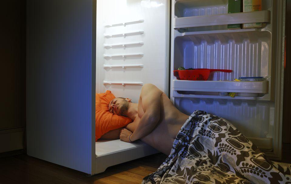 Man sleeping with head inside an open refrigerator