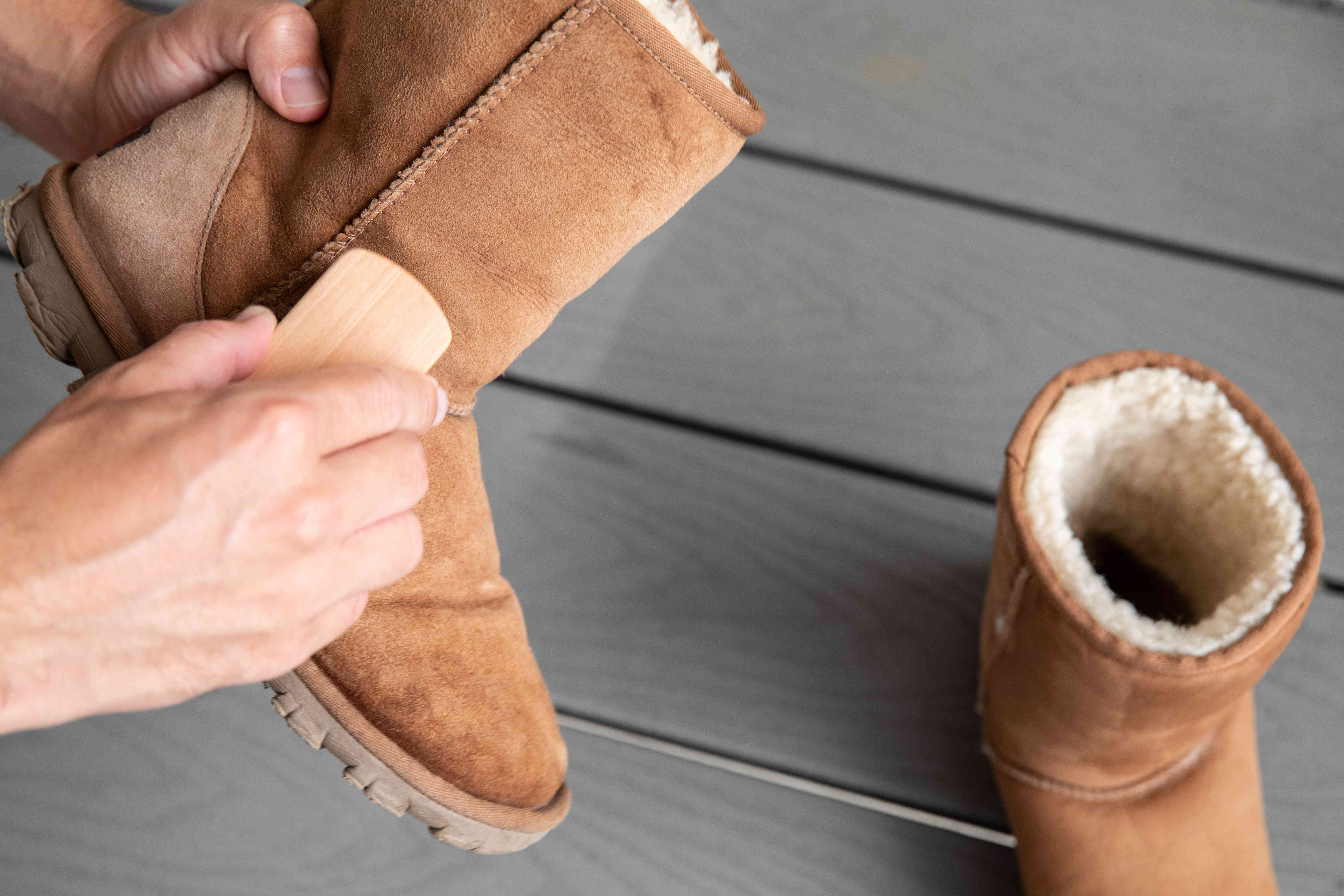 Someone brushing away scuff marks on Ugg boots