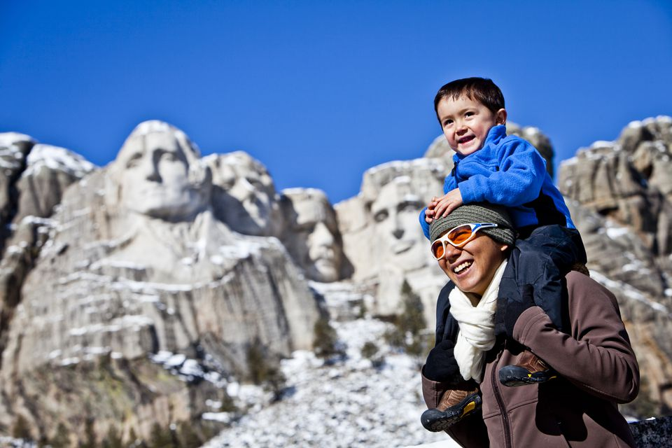 Japanese-American woman stands in front of Mt Rushmore National Memorial while carrying on her shoulders her son