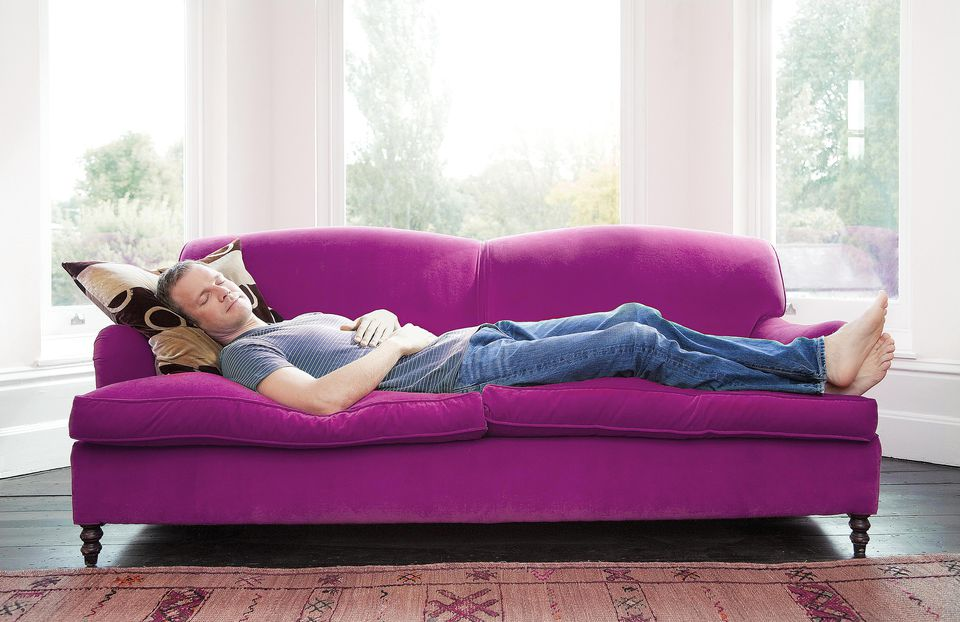 Man napping on purple couch