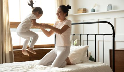 Mother holding jumping daughter on mattress