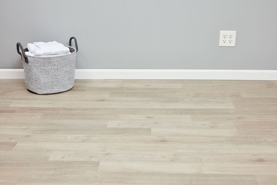 Laminate flooring installed with to white baseboard and linens basket