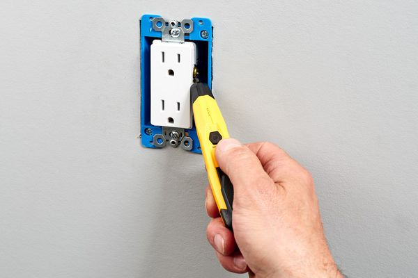 Person using a voltage tester on an outlet