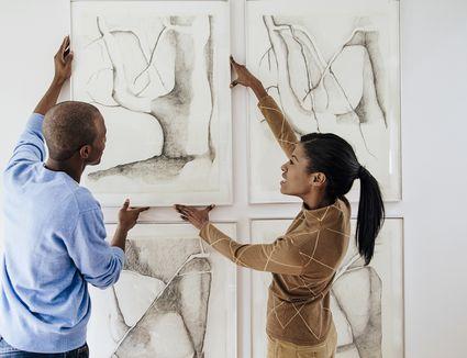 Mid-adult heterosexual couple hanging prints on wall