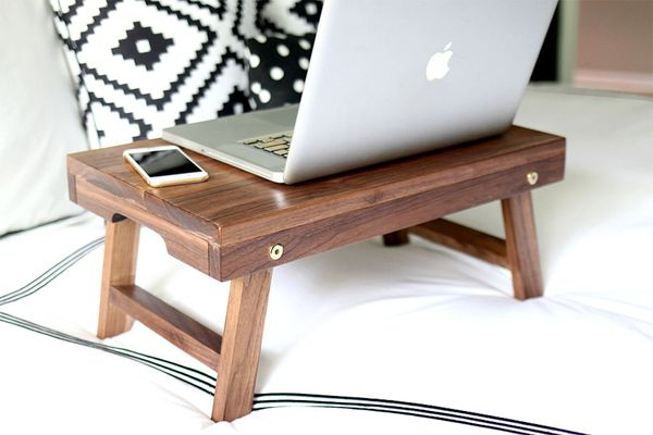 A laptop on a wooden stand on a bed