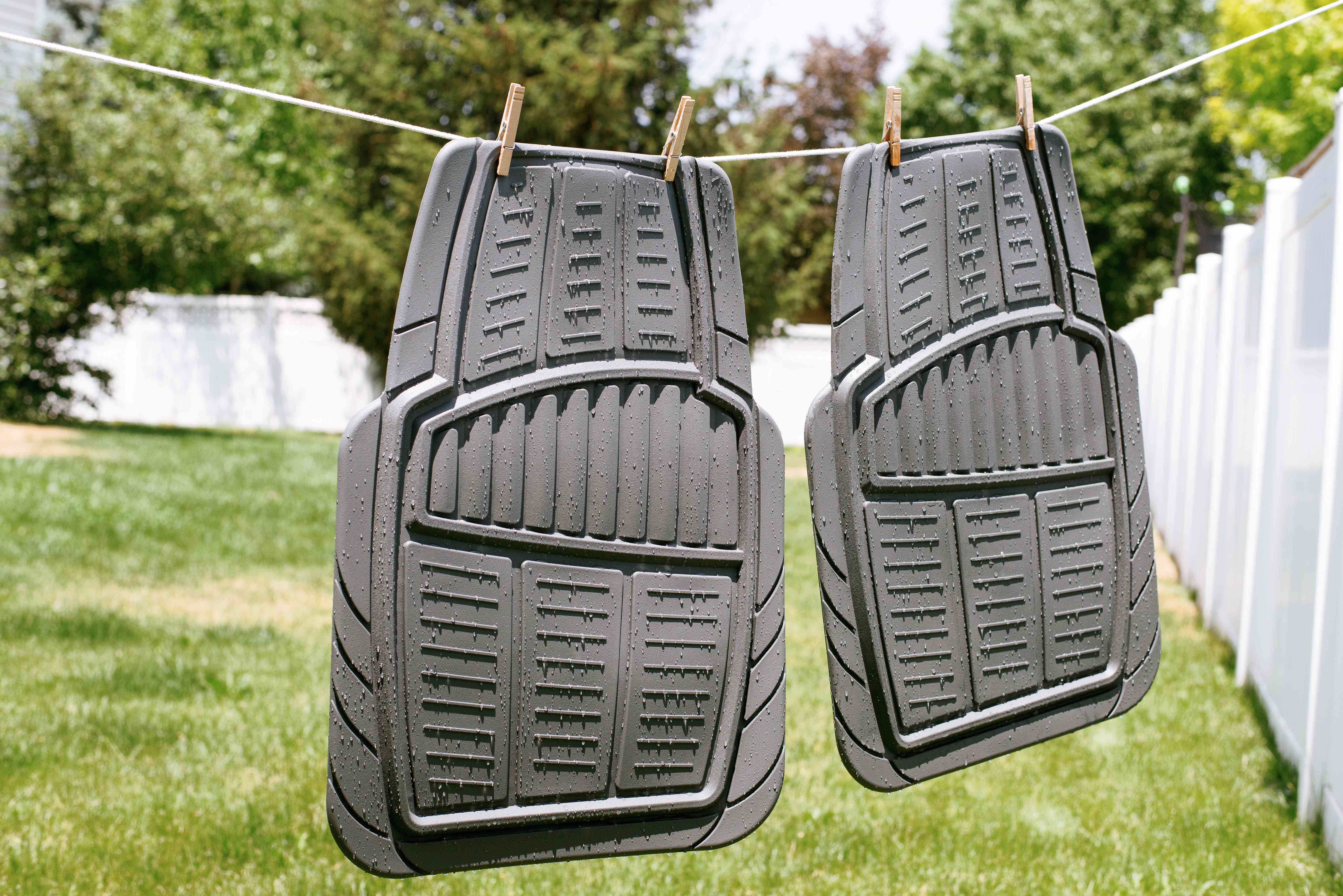 Gray rubber car mats hanging dry on clothesline