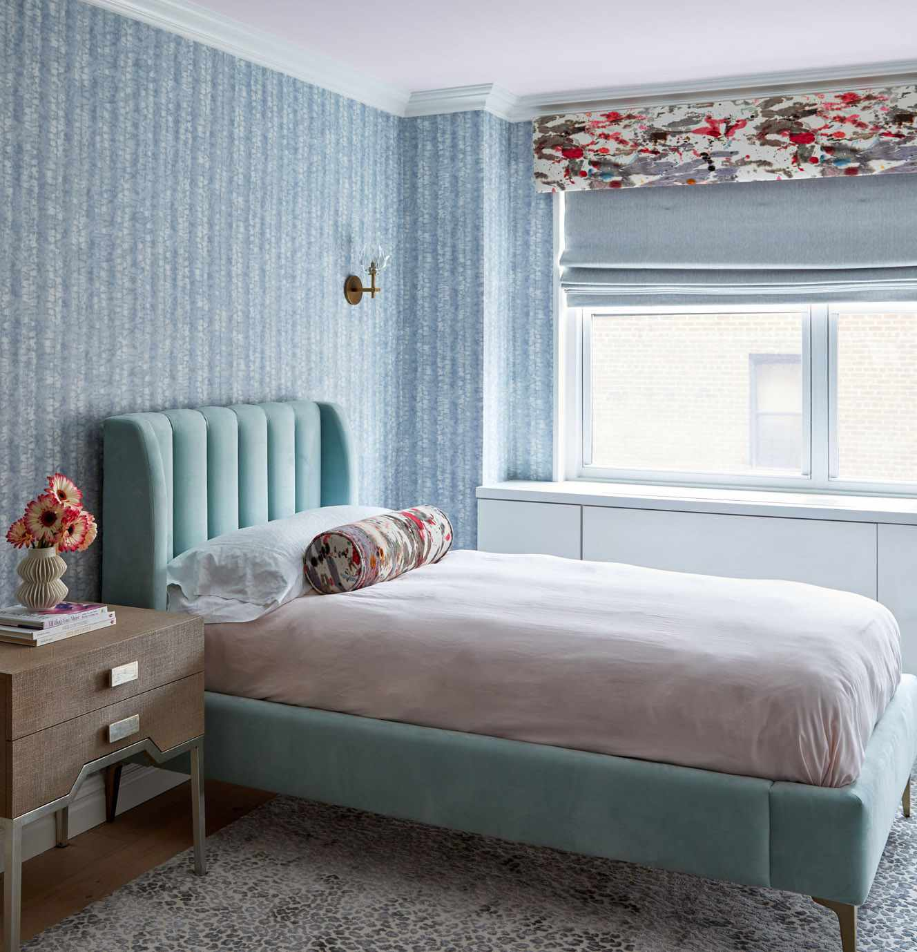 small bedroom with subtle blue pattern wallpaper and solid color bedding