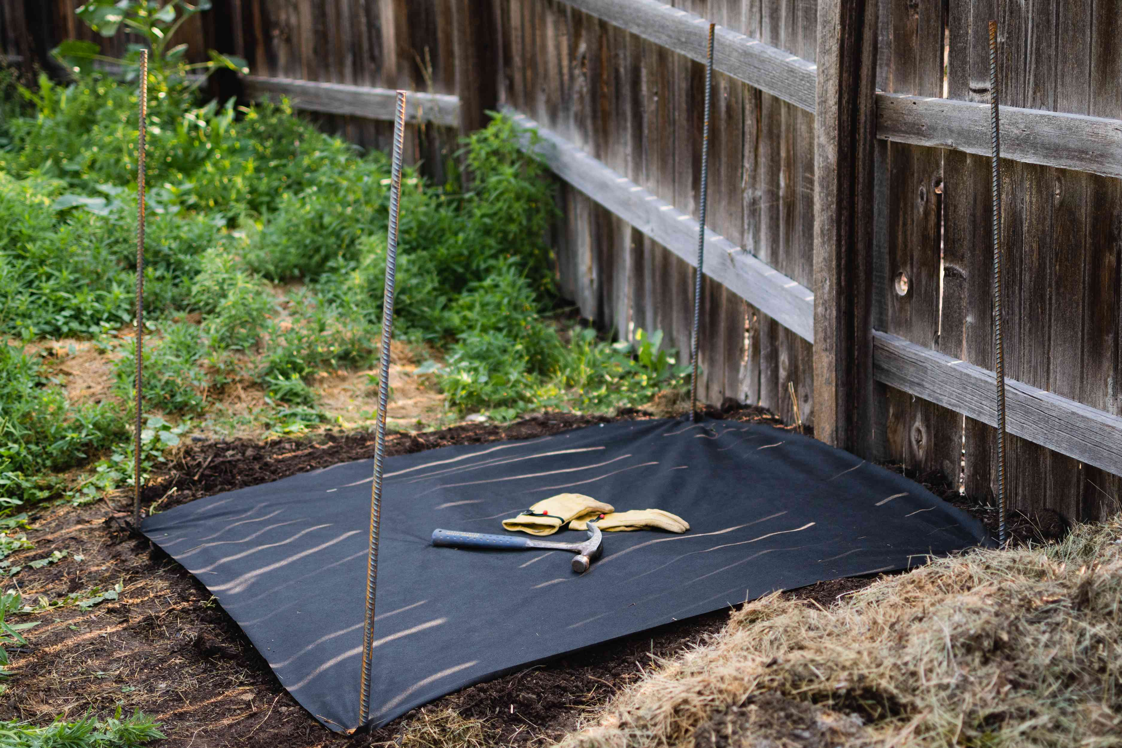 Rebar poles staked in each corner of weed cloth of composting location
