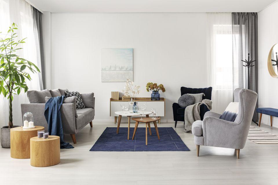 Interior de la sala de estar gris y azul marino con cómodos sofás y sillones.