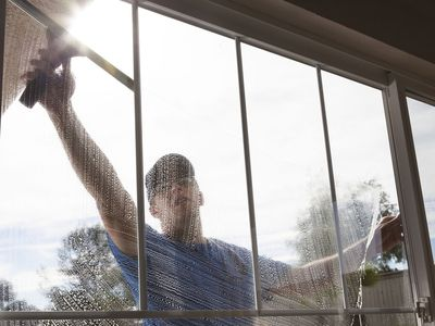 Man cleaning window of a home