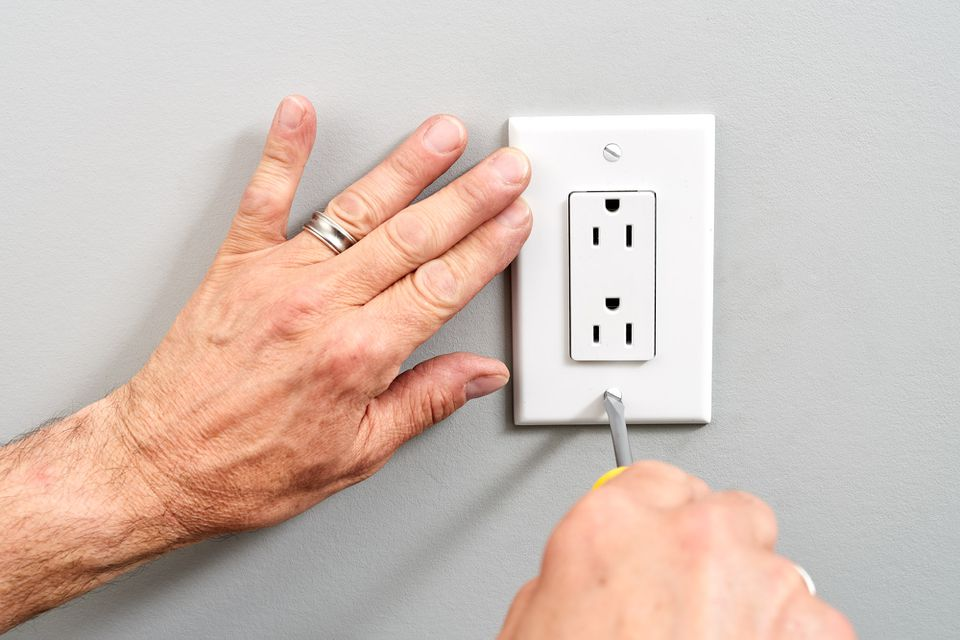 Upside-down outlet being replaced with screwdriver