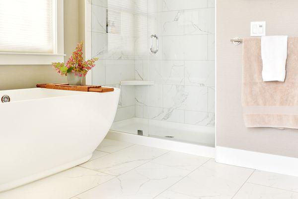 Bathroom with tan and light gray marble tile around white tub closeup