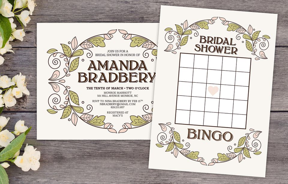 A bridal shower bingo card and bridal shower invitation on a wooden table surrounded by flowers.