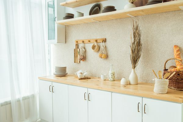 Interior of kitchen in rustic style. White furniture and wooden decor in bright cottage indoor