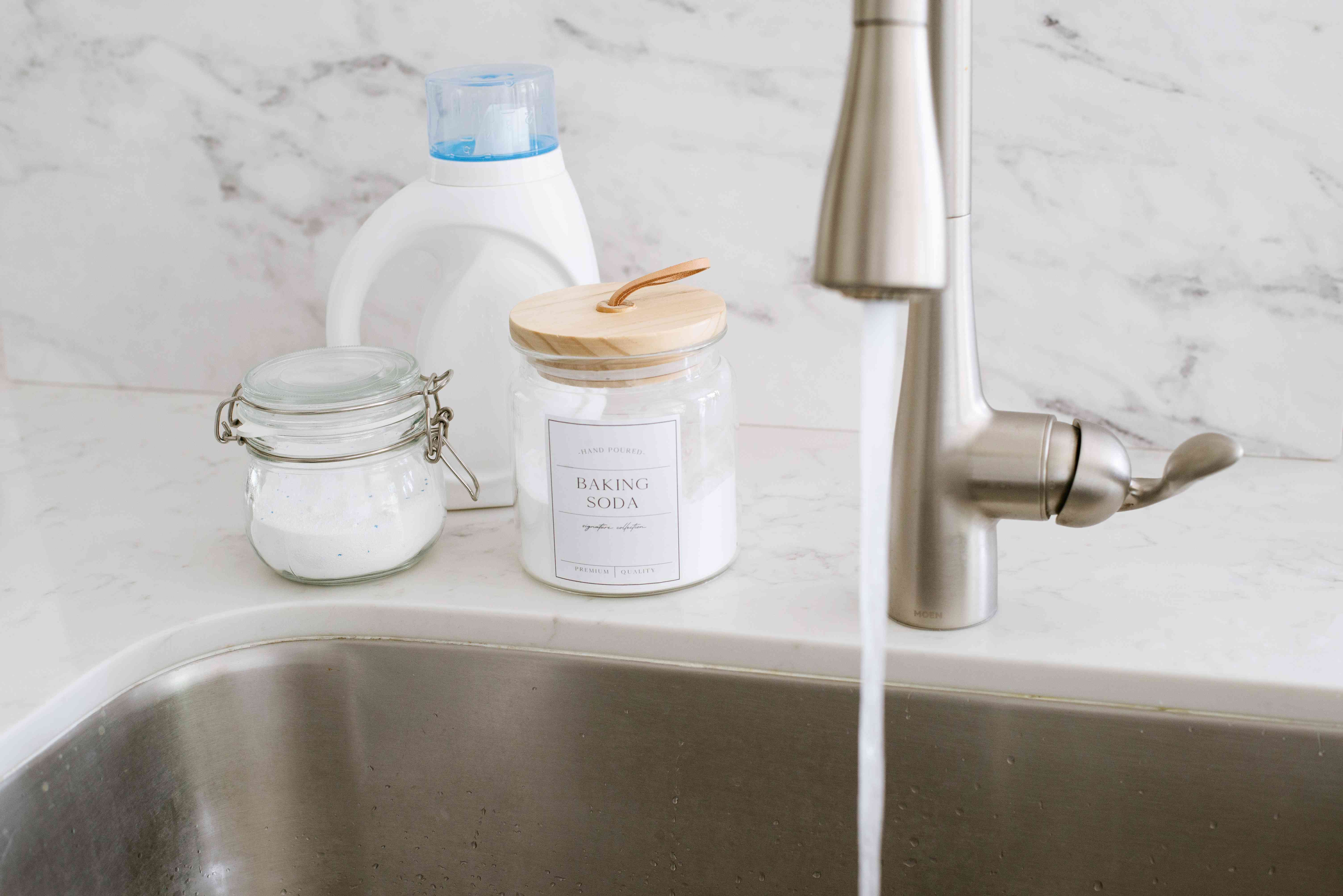 Baking soda and oxygen-based black in glass containers next to sink and laundry detergent bottle