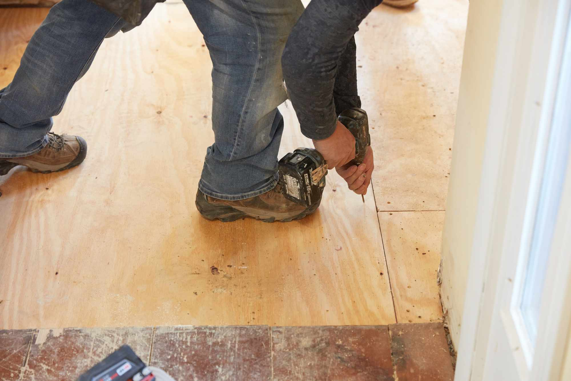 Exterior-grade plywood drilled into floor for ceramic tiles