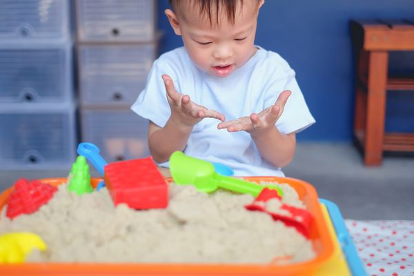 kid looking at his hands in over a sandbox